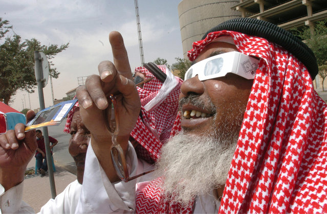 An elderly Saudi wearing protective glasses watches the partial solar eclipse in Riyadh, 29 March 2006. The fourth total eclipse of the 21st century took place. The umbra was tracking eastward at dizzying speed across Africa and parts of the Middle East before expiring in Asia, covering a distance of 14,500 kilometers (9,000 miles) where the eclipse would end at 11:48 GMT. (Photo by Fahd Shadeed/AFP Photo)