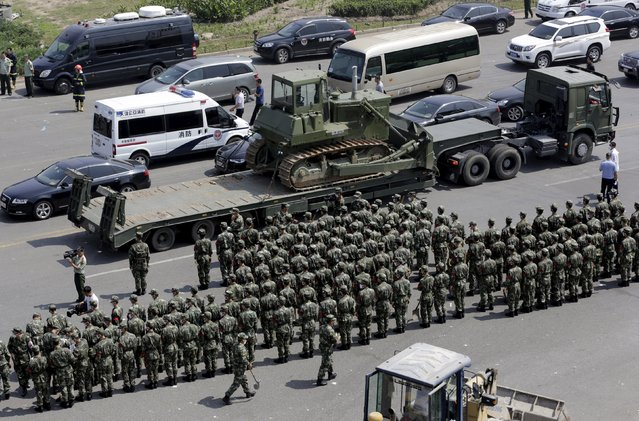 Paramilitary police stand in formation outside the site of the explosions at the Binhai new district, Tianjin, August 13, 2015. (Photo by Jason Lee/Reuters)