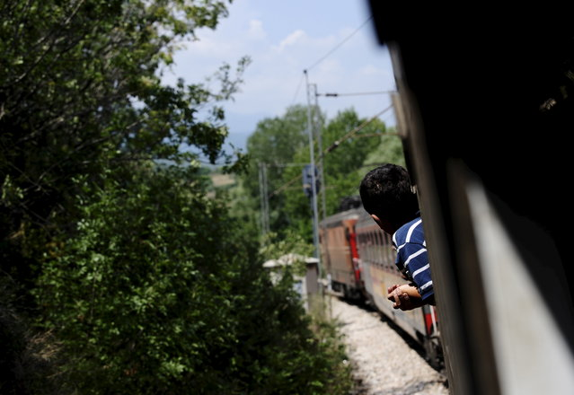A migrant boy looks out of the train window as he travels through Macedonia August 2, 2015. (Photo by Ognen Teofilovski/Reuters)