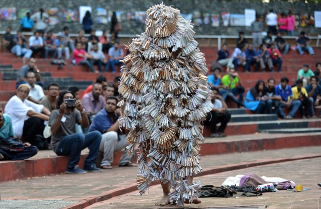 A Sri Lankan activist, who wrapped himself with fire crackers, walks in Colombo on July 23, 2014 to symbolically demonstrate against people burned during Anti-Tamil riots on the island thirty-one years ago. Official accounts placed the death toll at 400 while human rights activists put the toll at thousands. (Photo by Ishara S.Kodikara/AFP Photo)