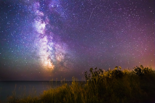 Milky Way pictured above the coast on July 4, 2014 in Isle of Wight, UK. The Milky Way shines in mesmerizing colourful patterns above the Isle of Wight in stunning photographs. (Photo by Chad Powell/Barcroft Media)