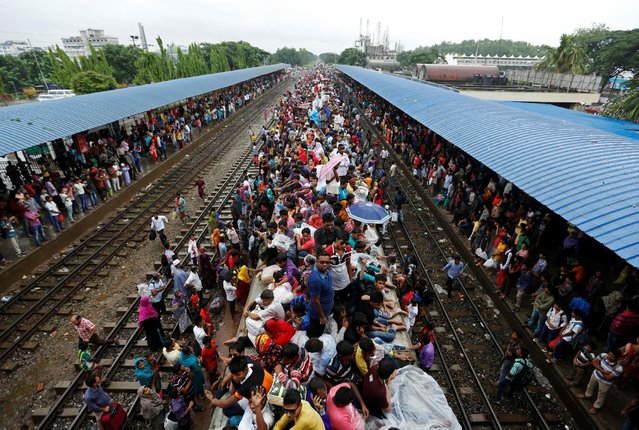 People sit atop of an overcrowded passenger train as they travel home to celebrate Eid al-Fitr festival, which marks the end of the Muslim holy fasting month of Ramadan, at a railway station in Dhaka, Bangladesh, July 5, 2016. (Photo by Adnan Abidi/Reuters)
