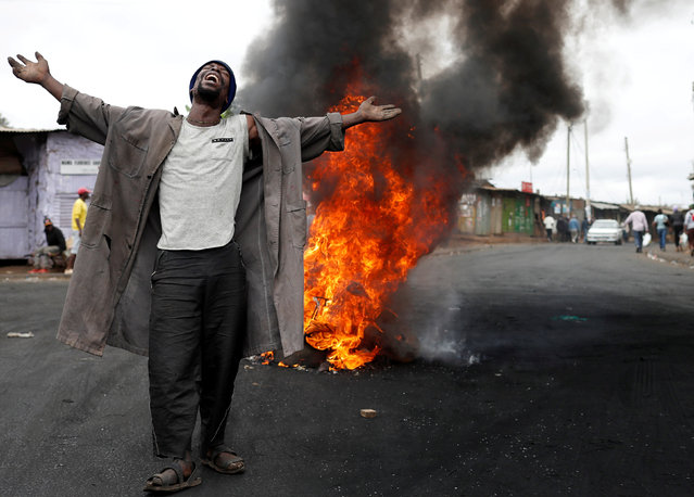 A supporter of opposition leader Raila Odinga gestures in front of a burned barricade in Kibera slum in Nairobi, Kenya, August 14, 2017. (Photo by Goran Tomasevic/Reuters)
