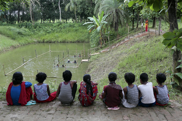 In this July 14, 2017 photo, Bangladeshi children attend a swimming training session, as others watch at a pond in the Shishu Polli Plus area in Sreepur village, near Dhaka, Bangladesh. (Photo by A.M. Ahad/AP Photo)