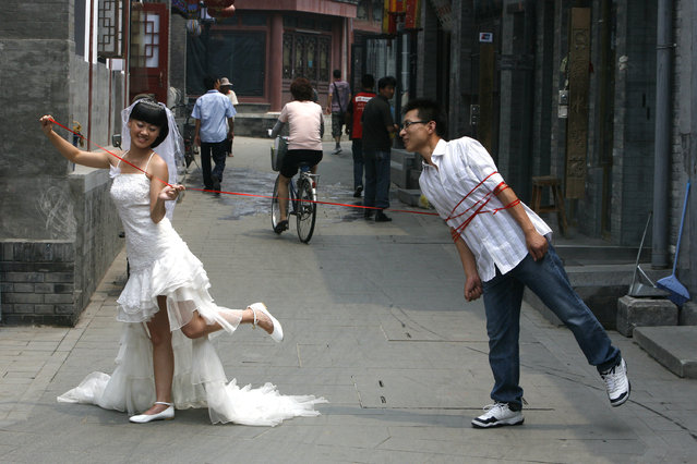 """A Chinese couple pose for a wedding photo on a busy alleyway or """"hutong"""" in Beijing July 7, 2008. Marriage registration offices in Beijing predict more than 9,000 couples will get married on August 8 2008, state media reported. The number eight is auspicious in Chinese, as it is pronounced like the word """"fa"""", which is part of the expression meaning """"to get wealthy"""". (Photo by Claro Cortes IV/Reuters)"""