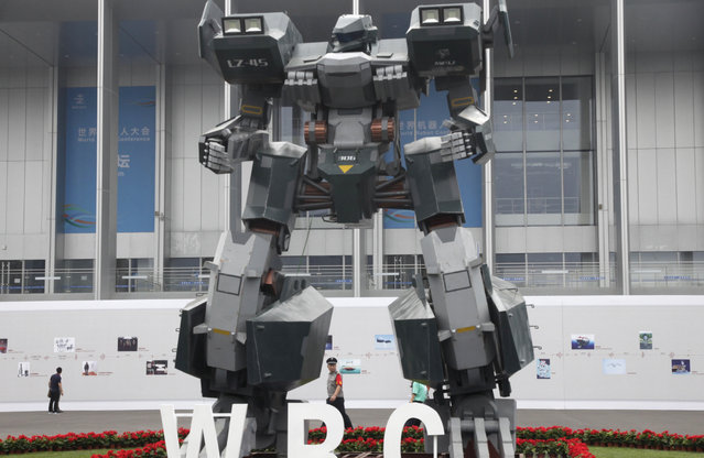 A security guard walks past a giant robot displayed at the World Robot Conference held in Beijing, China, Tuesday, August 22, 2017. (Photo by Fu Ting/AP Photo)