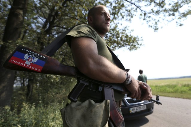 A pro-Russian separatist guards a checkpoint near the village of Rozsypne in the Donetsk region August 4, 2014. Ukrainian government forces recaptured an important railway hub from pro-Russian rebels in the east of the country, with five soldiers killed and 15 others wounded over the last 24 hours, a security official in Kiev said on Monday. (Photo by Sergei Karpukhin/Reuters)
