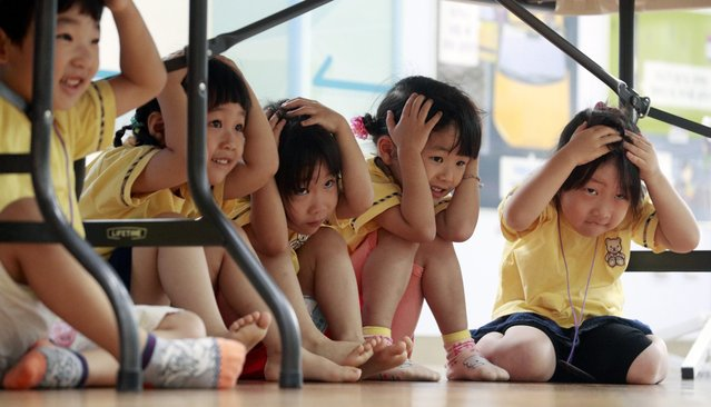 Preshoolers hide under their desk during an earthquake drill at a kindergarten in Seoul, South Korea, 13 July 2016. Last week, a magnitude 5.0 earthquake occurred near South Korea's southeastern city of Ulsan, but it caused no fatalities or serious damage. (Photo by EPA/Yonhap)