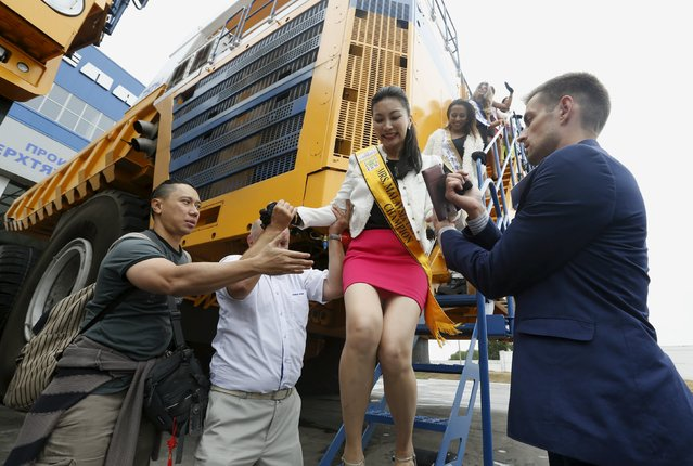 """Participants in the """"Mrs Universe 2015"""" contest are helped as they alight from a truck after posing for a photo at the Belarusian Autoworks (BELAZ) plant during their visit in Zhodino, Belarus, August 26, 2015. (Photo by Vasily Fedosenko/Reuters)"""