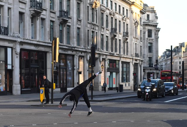 A person does a cartwheel in Oxford Circus during rush hour as the spread of the coronavirus disease (COVID-19) continues, London, Britain, March 23, 2020. (Photo by Dylan Martinez/Reuters)