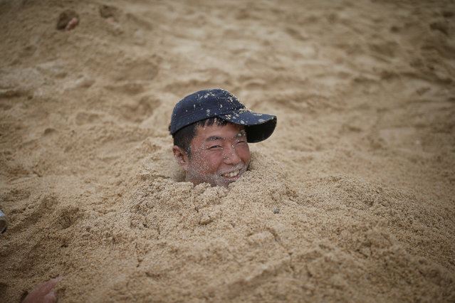 A tourist is buried in sand during the Boryeong Mud Festival at Daecheon beach in Boryeong, South Korea, July 16, 2016. (Photo by Kim Hong-Ji/Reuters)
