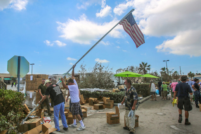 Marines and Sailors with the 26th Marine Expeditionary Unit help distribute food, water, and supplies in support of the Federal Emergency Management Agency in the aftermath of Hurricane Irma as citizens raise a flag at a distribution point in Key West, Florida, U.S. September 14, 2017. (Photo by Cpl. Jon Sosner/Reuters/U.S. Marine Corps)