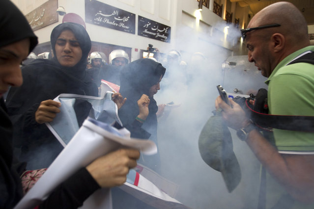 Reuters photographer Ahmed Jadallah and protesters react after police used a flashbang sound grenade during an anti-government rally demanding the release of human rights activist Abdulhadi al-Khawaja in Manama April 18, 2012. (Photo by Darren Whiteside/Reuters)