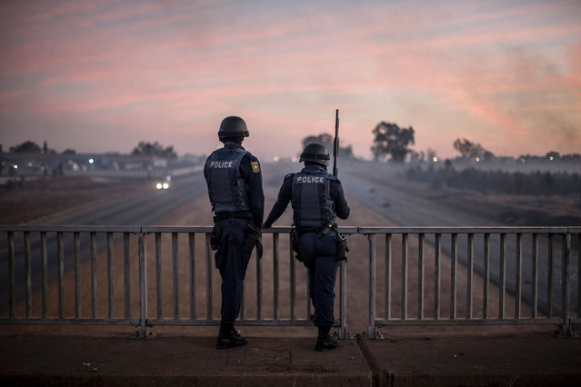 South African anti riot policemen stand guard a bridge on July 21, 2016 as protesters bloc a highway in Meyerton, during a service delivery protest ahead of the August 3rd municipal elections. (Photo by Marco Longari/AFP Photo)