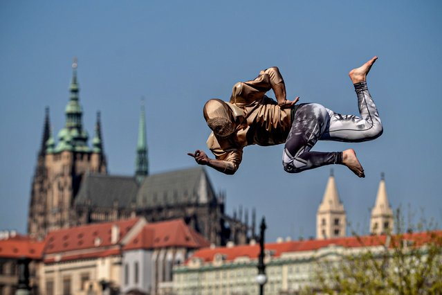 A member of the contemporary circus company Cirk La Putyka perform on the mobile trampoline as he amuses local residents in Prague, Czech Republic, 09 April 2020. The aim of the Cirk La Putyka events in the streets of Czech capital is to get live art back to people during the lockdown. According to them, when people can't go to the artists, to the theater, the actors go to the people. The Czech government has imposed a lockdown in an attempt to slow down the spread of the pandemic COVID-19 disease caused by the SARS-CoV-2 coronavirus. (Photo by Martin Divisek/EPA/EFE)
