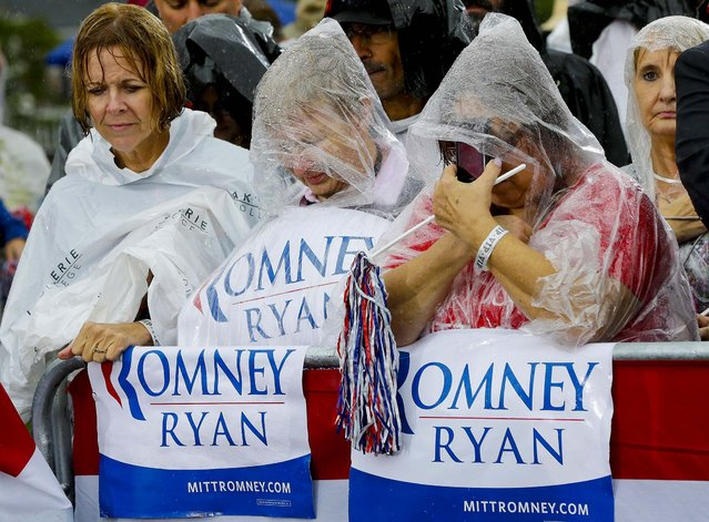 Supporters bow their heads as Republican presidential candidate and former Massachusetts Governor Mitt Romney holds a moment of silence for the embassy officials killed in Libya, as he campaigns in the rain at Lake Erie College in Painesville, Ohio. (Photo by Charles Dharapak/Associated Press)
