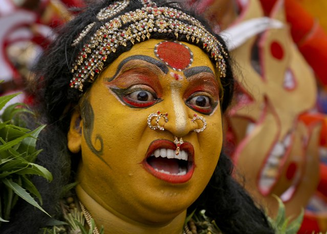 "An Indian artist dressed as Hindu goddess Mahakali performs during a procession marking ""Bonalu"" festival in Hyderabad, India, Monday, August1, 2016. Bonalu is a month long Hindu folk festival of India's Telangana region dedicated to Kali, the Hindu goddess of destruction. (Photo by Mahesh Kumar A./AP Photo)"