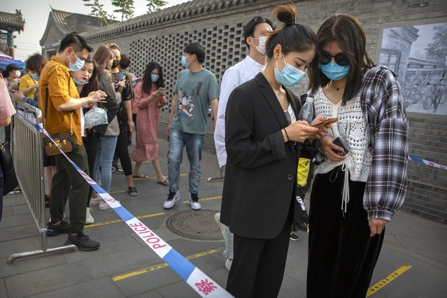People wearing face masks to protect against the new coronavirus use their smartphones to enter their personal data before being allowed to enter a pedestrian shopping street in Beijing, Saturday, May 16, 2020. (Photo by Mark Schiefelbein/AP Photo)