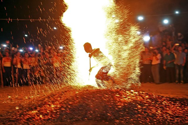 """A man runs through burning charcoal barefooted as he participates in a traditional ritual called """"Lianhuo"""", or """"fire walking"""", in Pan'an county, Zhejiang province September 17, 2014. Lianhuo, a traditional local ritual listed in 2005 as an """"intangible cultural heritage"""" of the province, involves dozens of men walking across burning charcoal or firewood barefooted, as a way to ward off evil and pray for good fortune. (Photo by Reuters/China Daily)"""