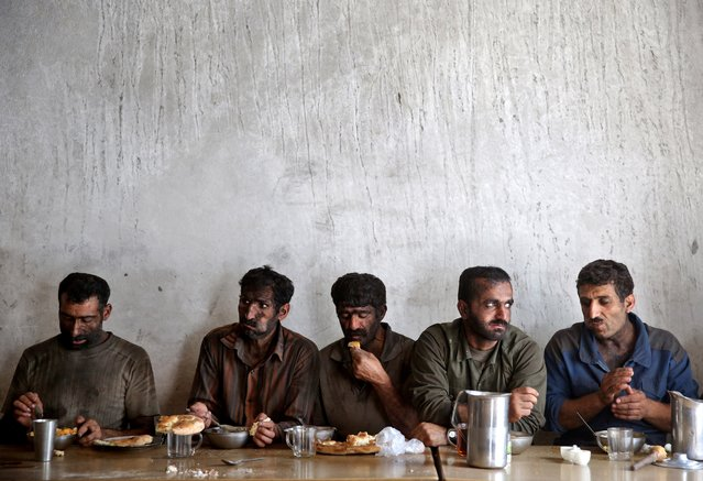 In this Tuesday, Aug. 19, 2014 photo, Iranian coal miners eat lunch at a mine near the city of Zirab 212 kilometers (132 miles) northeast of the capital Tehran, on a mountain in Mazandaran province, Iran. (Photo by Ebrahim Noroozi/AP Photo)