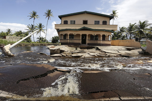 A house, badly damaged by flood water from the overflowing Nariva swamp basin following two days of rainfall in the country, sits precariously on the edge of Manzanilla Mayaro Road, on Trinidad's East coast November 17, 2014. (Photo by Andrea De Silva/Reuters)