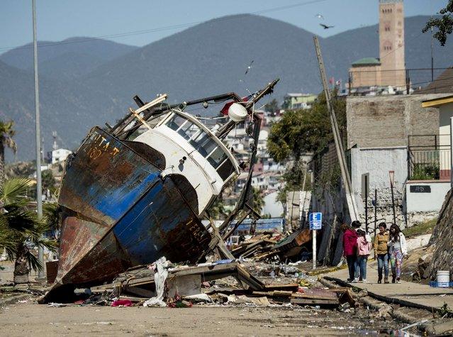 A fishing boat that was ran aground by the sea while moored in the port of Coquimbo, some 445 km north of Santiago, during the eve's earthquake on September 17, 2015. A million people were evacuated in Chile after an 8.3-magnitude quake struck offshore in the Pacific, killing at least 10 people and triggering tsunami waves along its northern coast. (Photo by Martin Bernetti/AFP Photo)