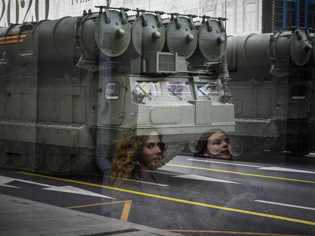 A picture taken through a window shows the reflections of women passing in front of Russian military vehicles during a rehearsal for the WWII Victory Parade in Moscow on June 17, 2020. Russia's President Putin on June 24 will preside over a massive military parade to mark Soviet victory in World War II, which was postponed due to the coronavirus pandemic. (Photo by Dimitar Dilkoff/AFP Photo)