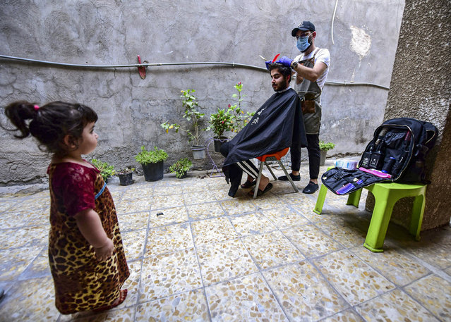 Iraqi itinerant barber Hussain Majid (R) wears a face mask as he gives a haircut to a client at his house in Baghdad, Iraq, 20 May 2020. Cutting the hair of clients at their houses is a precaution barbers turned to, to earn a living during the coronavirus pandemic in Iraq, after the Iraqi authorities have closed the barbers salons and other commercial activities to prevent the spread of the COVID-19 disease. (Photo by Murtaja Lateef/EPA/EFE/Rex Features/Shutterstock)
