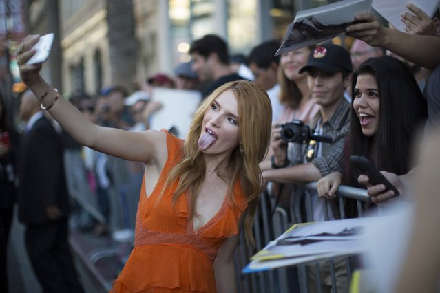 """Cast member Bella Thorne poses with a fan at the premiere of """"Alexander and the Terrible, Horrible, No Good, Very Bad Day"""" at El Capitan theatre in Hollywood, California October 6, 2014. The movie opens in the U.S. on October 10. (Photo by Mario Anzuoni/Reuters)"""