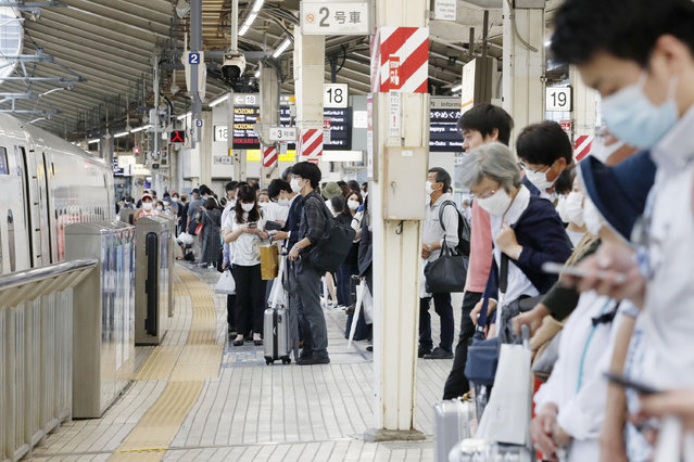 Passengers wait for a bullet train at Tokyo station Friday, June 19, 2020. All domestic restrictions were removed Friday and people can now start travel anywhere in Japan. (Photo by Kyodo News via AP Photo)