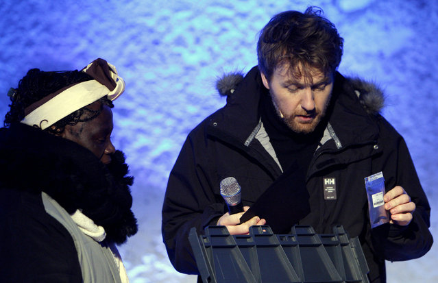 The Norwegian host Fredrik Skavland (R) shows a small plastic bag containing seeds as Kenyan environmentalist and Nobel Peace Prize winner Wangari Maathai (L) looks on during The opening of the Global Seed Vault on February 26, 2008 in Longyearbyen. (Photo by Daniel Sannum Lauten/AFP Photo)