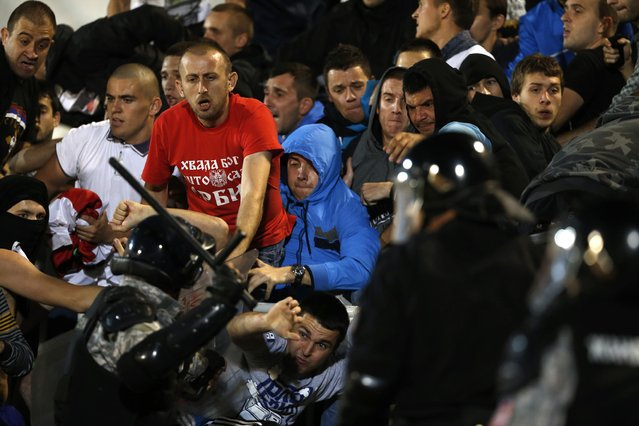 Serbian riot police clashes with Serbian national team supporters during the Euro 2016 Group I qualifying match between Serbia and Albania, at the Partizan stadium in Belgrade, Serbia, Tuesday, October 14, 2014. (Photo by Marko Drobnjakovic/AP Photo)