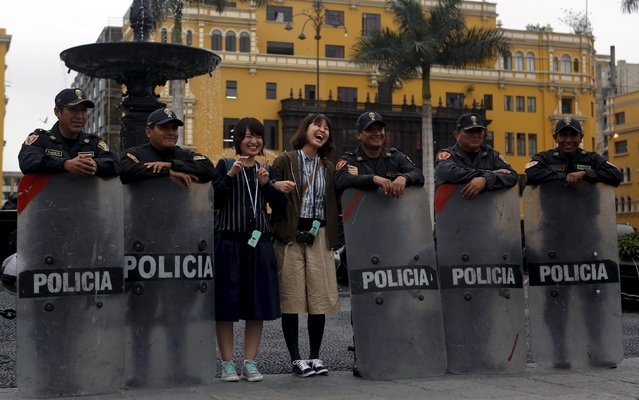 Japanese tourist pose for a photo with Peruvian anti-riot police in Lima's main square in down town Lima, September 23, 2015. (Photo by Mariana Bazo/Reuters)