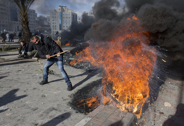 A Palestinian protester burns tires during clashes with Israeli troops following protests against U.S. President Donald Trump's decision to recognize Jerusalem as the capital of Israel, in the West Bank city of Ramallah, Thursday, December 7, 2017. (Photo by Nasser Nasser/AP Photo)
