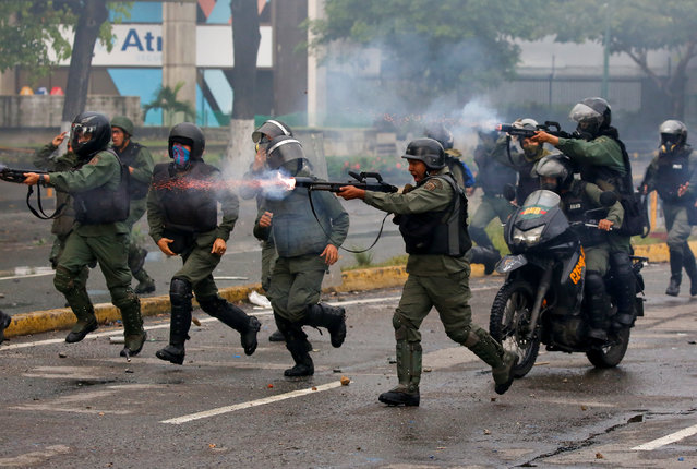 """Riot security forces take up positions while clashing with demonstrators rallying against Venezuela's President Nicolas Maduro's government in Caracas, Venezuela, July 28, 2017. Venezuelans have been protesting against Maduro to demand him to respect the opposition-led Congress and resolve chronic food and medicine shortages that have fuelled malnutrition and health problems. Carlos Garcia Rawlins: """"Security forces, often angry and frustrated, began firing directly at protesters"""". (Photo by Carlos Garcia Rawlins/Reuters)"""