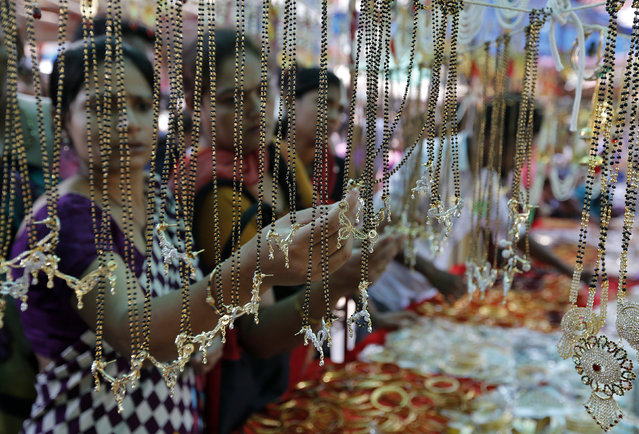 Women buy artificial jewellery at an open air market ahead of the Hindu festival of Diwali, in the western Indian city of Ahmedabad October 19, 2014. (Photo by Amit Dave/Reuters)