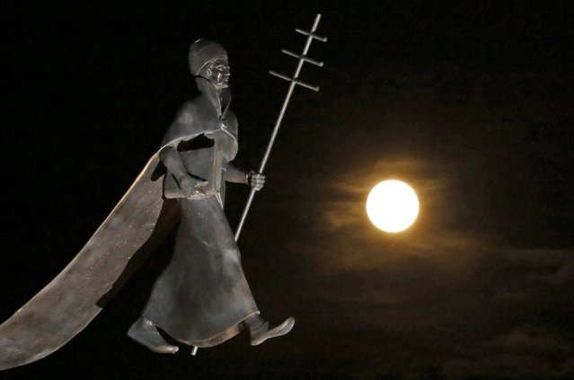 A full moon, the last of this year's supermoons, rises near a statue of Pope Leon IX in Eguisheim, Eathern France, September 27, 2015. This larger-than-average full moon is seen in France on Sunday, hours before a total lunar eclipse which will occur during the early hours of Monday, when the shadow of the Earth casts a reddish glow on the moon, the result of a rare combination of an eclipse with the closest full moon of the year. (Photo by Jacky Naegelen/Reuters)