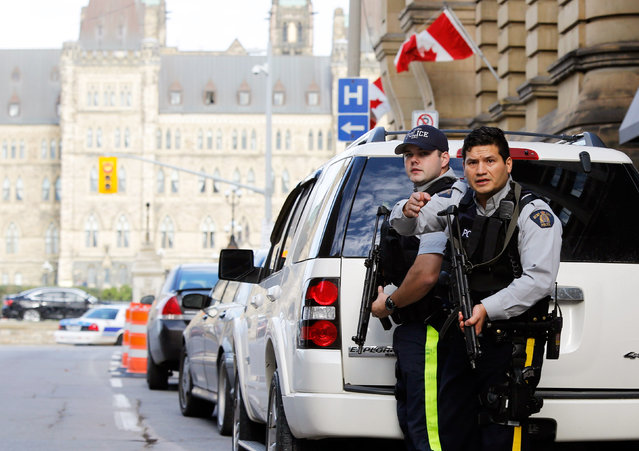 Armed RCMP officers guard access to Parliament Hill following a shooting incident in Ottawa October 22, 2014. (Photo by Chris Wattie/Reuters)