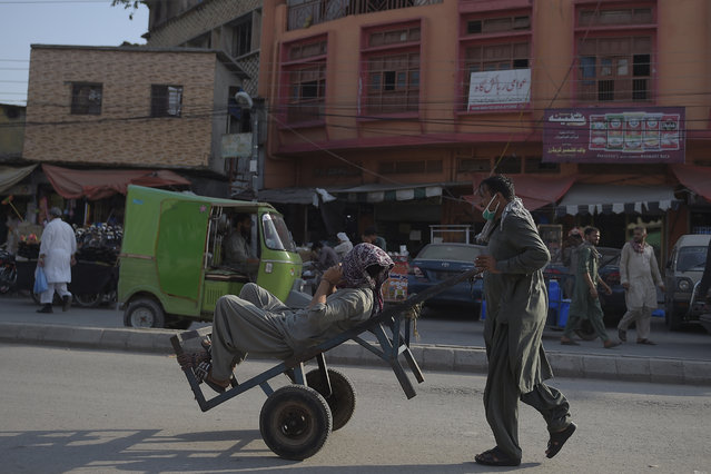 A labourer pulls his cart while another sits on it during work hours in Rawalpindi on July 14, 2020. (Photo by Farooq Naeem/AFP Photo)