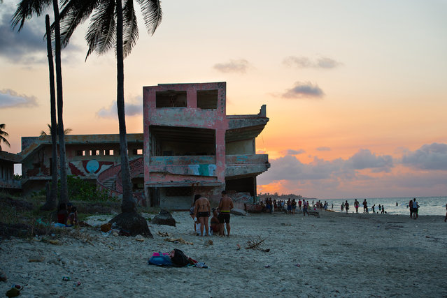 Cubans enjoy a warm April evening in the seaside beach town of Guanabo which is about 20 miles East of Havana. An abandoned low rise hotel sits on the beachfront which is experiencing sand loss and dune damage. The government has made the recovery of this beach a priority and some government and private homes are already being demolished. In some cases, new buildings will be built. (Photo by Sarah L. Voisin/The Washington Post)