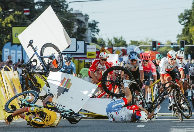 Dutch cyclist Fabio Jakobsen's bicycle (behind, L) flies through the air as he collides with compatriot Dylan Groenewegen (on the ground, L) during the opening stage of the Tour of Poland race in Katowice, southern Poland on August 5, 2020. The Dutch rider was fighting for his life on Wednesday after he was thrown into and over a barrier at 80km/h in a sickening conclusion to the opening stage of the Tour of Poland. (Photo by Szymon Gruchalski/Forum/AFP Photo)