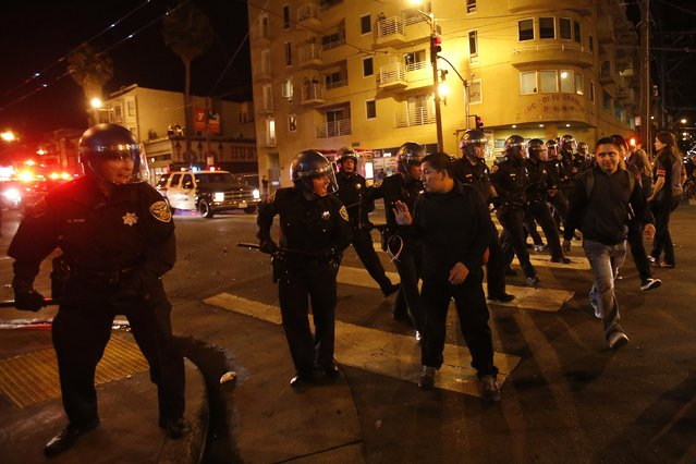 Police officers disperse a crowd in the Mission District, in San Francisco, California October 29, 2014. (Photo by Stephen Lam/Reuters)