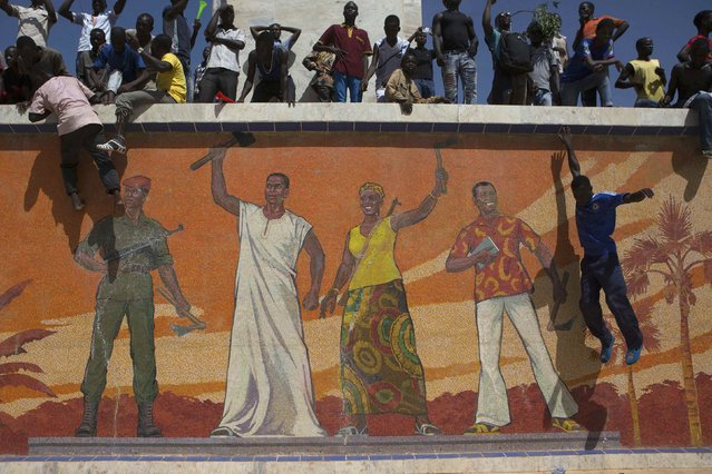A protestor jumps from a ledge in front of a mural at Place de la Nation in Ouagadougou, capital of Burkina Faso, October 28, 2014. Police fired tear gas at rock-throwing protesters after tens of thousands of people marched through the capital of Burkina Faso on Tuesday morning, calling for President Blaise Compaore to abandon plans to hold a referendum on changing term limits to allow him to stay in power. (Photo by Joe Penney/Reuters)