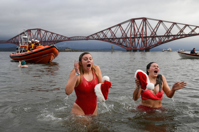 Members of the public wearing fancy dress react to the water as they join around 1100 New Year swimmers, many in costume, in front of the Forth Rail Bridge during the annual Loony Dook Swim in the River Forth on January 1, 2018 in South Queensferry, Scotland. Tens of thousands of people gathered last night in Edinburgh and other events across Scotland to see in the New Year at Hogmanay celebrations. (Photo by Jeff J. Mitchell/Getty Images)