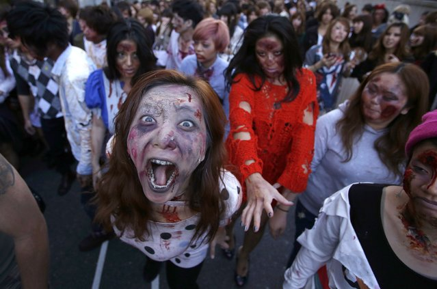 """Participants wearing costumes and make-up as zombies march during a Halloween event to promote the U.S. TV series """"The Walking Dead"""" at Tokyo Tower October 31, 2013. (Photo by Issei Kato/Reuters)"""