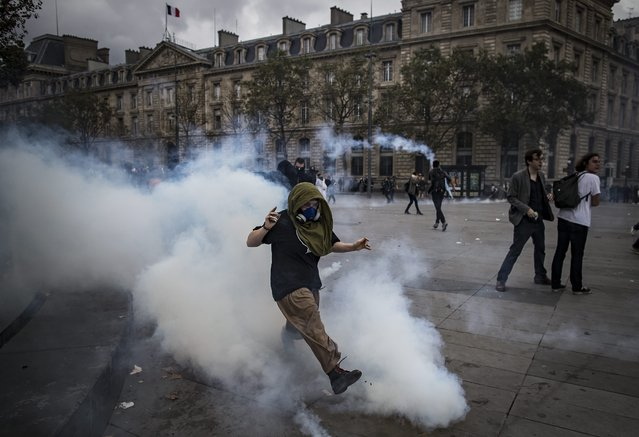 A protester kicks back a tear gas canister at French Riot Police during a demonstration against the new labor law in Paris, France, 15 September 2016. (Photo by Ian Langsdon/EPA)