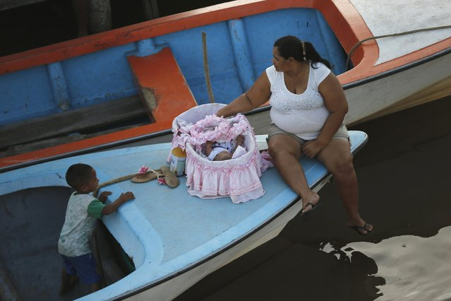 A family travels in a boat on Lake Maracaibo, between houses on stilts, in the village of Congo Mirador in the western state of Zulia October 21, 2014. (Photo by Jorge Silva/Reuters)