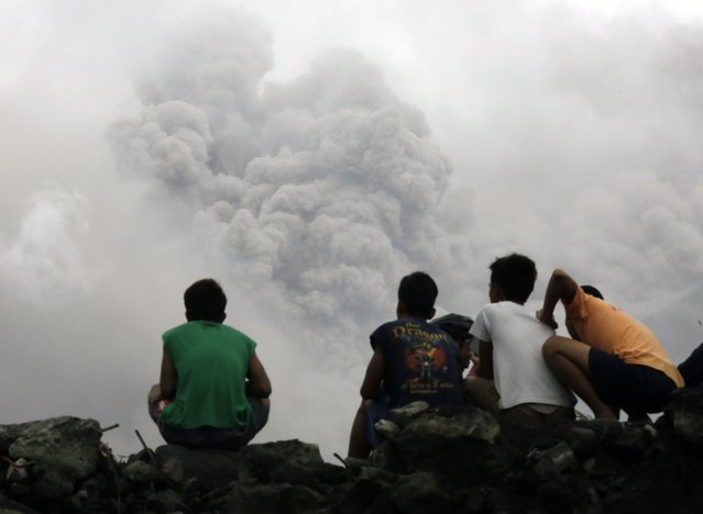 Filipino villagers sit along the slopes of rumbling Mayon Volcano as it spews ash in Legaspi city, Albay province, Philippines, January 16, 2018. (Photo by Francis R. Malasig/EPA/EFE/Rex Features/Shutterstock)