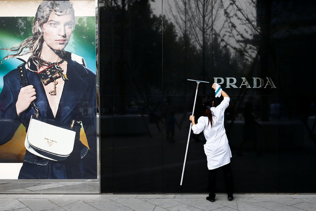A woman cleans the brand logo at a Prada fashion boutique in Beijing, China, September 16, 2016. (Photo by Thomas Peter/Reuters)