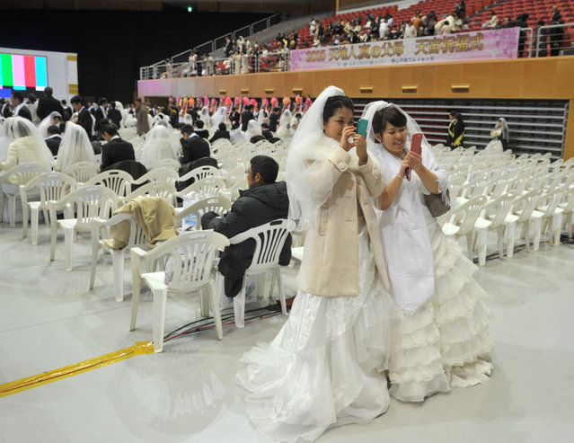 """Two brides look at their mobile phones during a mass wedding organised by the Unification Church in Gapyeong on February 17, 2013. Some 3,500 couples married in a mass wedding organised by the Unification Church on February 17 – the first such event since the death of their """"messiah"""" and controversial church founder Sun Myung Moon. (Photo by Kim Jae-Hwan/AFP Photo)"""